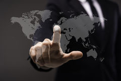 Business man touching imaginery screen with world map. Business man in black suit touching imaginery screen with world map Royalty Free Stock Photography