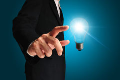 Business man touching light of idea Stock Photography