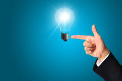 Business man touching light of idea Stock Photo