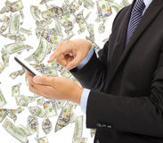 Business man touching smart phone with money rain Stock Images