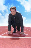 Business Man on a Track with Clouds. A business man is starting a race / competition on a red track. This photo can represent a variety of ideas from competition Royalty Free Stock Images