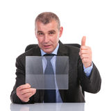 Business man with transparent pannel shows thumb up. Business man at the desk, holding a transparent pannel and showing thumb up to the camera. on a white Stock Photos