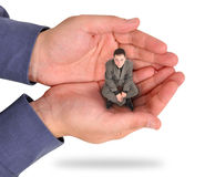Business Man Trapped in Hand. A business man is sitting in the palm of his bosses hand on a white background. He looks unhappy and feels trapped and weak at his Stock Image