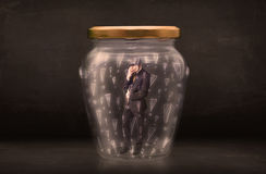 Business man trapped in jar with exclamation marks concept Stock Photos