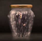 Business man trapped in jar with exclamation marks concept Stock Image