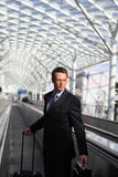 Business man travel with bag and trolley on escalators Stock Photo