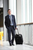 Business man travel with trolley. Look through the windows Royalty Free Stock Photography