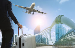 Business man and traveling luggage in city life with plane flyin Stock Photography