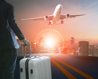 Business man and traveling luggage standing against skyline and. Passenger plane taking over airport runway Stock Photography