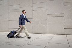 Business man in suit walking with trolley at the airport Stock Image