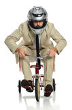 Business Man on Tricycle. Business man with helmet riding child's tricycle isolated over white royalty free stock photography
