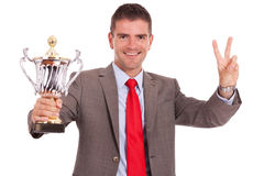 Business man with trophy and victory sign Royalty Free Stock Images