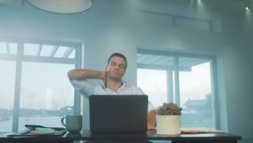 Business man trying to relax in luxury house. Tired man relaxing at workplace. Business man trying to relax after work on laptop computer in luxury house. Tired stock video footage