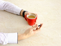 Business Man. Turning on his Cellphone while holding Coffee in a red Cup Royalty Free Stock Image