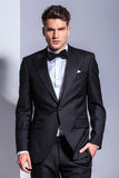 Business man in tuxedo holding his hand in pocket. Royalty Free Stock Image