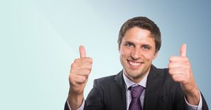 Business man two thumbs up against blue background. Digital composite of Business man two thumbs up against blue background Stock Photos