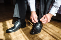 Business man tying shoe laces on the floor. Close-up royalty free stock images
