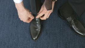 Business man tying shoe laces on the floor stock video footage