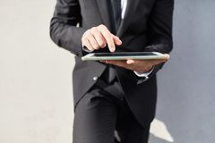 Business man type message on tablet computer. Business man types message on tablet computer outdoors stock images