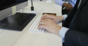 Business man typing on computer keyboard sitting at office desk working in creative open space with coworkers. Slow motion 60 stock footage