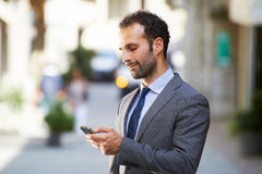 Business man typing sms on mobile phone in street Stock Photos