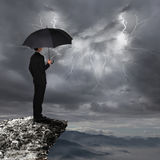 Business Man with umbrella look rainstorm cloud. Business Man with an umbrella look rainstorm clouds and lightning over danger precipice on the mountain Royalty Free Stock Images