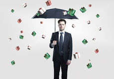 Business man with umbrella under gift boxes rain Royalty Free Stock Image