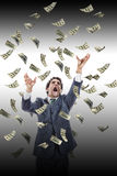 Business man under falling money banknotes screaming reaching fo Stock Images