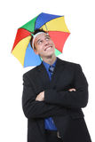 Business Man Under Umbrella. A handsome business man under a rainbow hat umbrella Royalty Free Stock Image