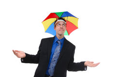 Business Man Under Umbrella. A handsome business man under a rainbow hat umbrella stock images