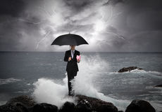 Business man under an umbrella in the sea. Business man under an umbrella standing on a rock in the sea with lightning sky, business concept Royalty Free Stock Photo