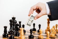 Business man unfair playing chess game. Business man hand holding dollar currency unfair playing chess game Stock Photos