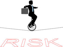 Business man unicycle tightrope financial risk. Business man rides a unicycle on a tightrope over financial risk Stock Photo