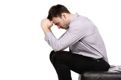 Business man sat in despair isolated on a white background. Business man upset sat with his head in his hands isolated on a white background Royalty Free Stock Images