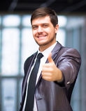 Business man in urban city holding thumbs up Royalty Free Stock Image