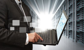 Business man use notebook. In server room Royalty Free Stock Photos