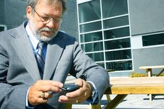 Business man using blackberry. Senior business man having  his computer pocket Stock Image