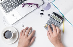 Business man using calculator on modern white office desk table Stock Photos