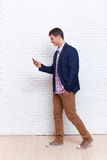 Business Man Using Cell Phone Smartphone Busy Walking Social Network Communication. Full Length Over White Brick Wall Stock Photo