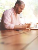 Business man using cell phone working. Young man chatting on his smart phone while sitting at wooden table with blur copy space for your text message, male Royalty Free Stock Image