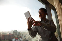 Business man using digital tablet. Young business man using digital tablet with window in hotel, asian Stock Image