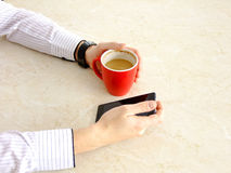Business Man. Using his Cellphone while holding Coffee in a red Cup Stock Image