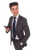 Business man using his phone for texting looks to side. Happy business man using his phone for sms texting looks to side and laughs on white studio background Royalty Free Stock Photos