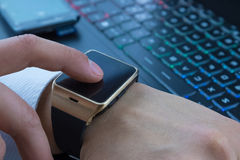 Business man using his smartwatch app near computer pc keyboard and smartphone on daily light Royalty Free Stock Image