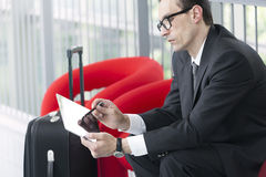 Business man using his Tablet at exhibition lobby. Business man with trolley using his Tablet on red armchair at exhibition lobby stock image