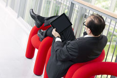 Business man using his Tablet on a red armchair Stock Photography