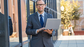Business man using laptop on a city street next to workplace. Royalty Free Stock Image