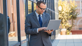 Business man using laptop on a city street next to workplace. Stock Photography