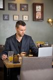 Business Man Using Laptop While Having Sandwich Stock Images