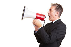 Business man using a megaphone. Elderly business man screaming loudly in a megaphone Royalty Free Stock Photography